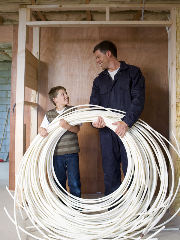 Man in coveralls and young boy holding electrical cables